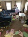 A young child in jumping in a living room full of toys and children's artwork