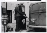 Abe Malmon at the pump of his gas station, St. Paul, Minnesota