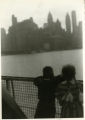 A girl and a boy looking toward the New York City skyline aboard the ship USAT (United States Army Transport)