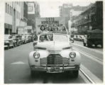 1941 Duluth State Teachers College Homecoming court riding in a car with banner in downtown Duluth