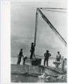 Construction of Glensheen pier and boathouse, with workers and crane