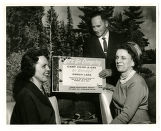 Joe Clifford of Midland Cooperatives, Lillian Ollila and Anne Lahti with a sign advertising Camp Co-op-a-gan, Virginia, Minnesota