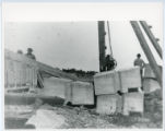 Construction of Glensheen pier and boathouse, workers with blocks and crane